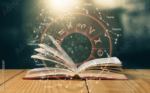 Photo Open book on old wooden table with astrology illustration