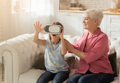Photo Smiling mature lady and her granddaughter in virtual reality headset at home