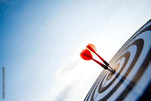 Close up shot red darts arrows in the target center on dark blue sky background Wallpaper Mural