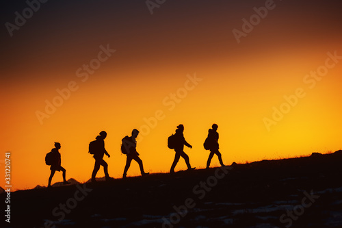 Canvas Print Five hikers going uphill at sunset