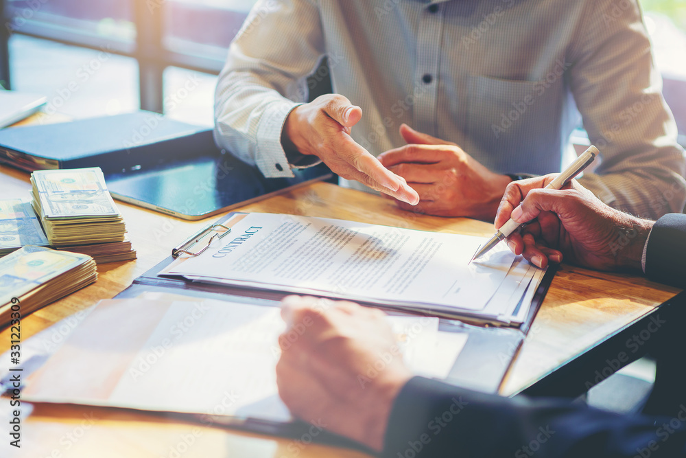 Fototapeta Businessman puts signature on contract at business meeting and passing money after negotiations with business partners.