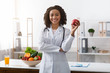 Pretty black lady dietologist holding apple in her hand