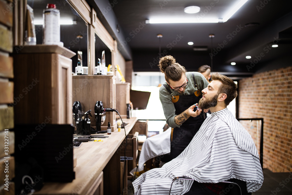 Fototapeta Client during beard and moustache grooming in barber shop