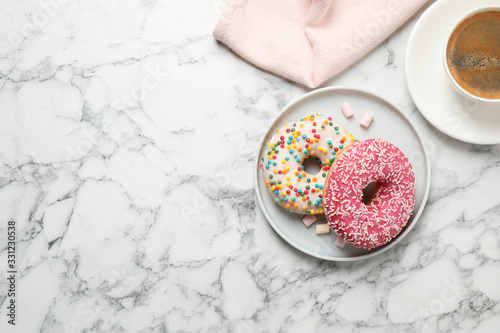 Fototapeta Yummy donuts with sprinkles and coffee on white marble table, flat lay. Space for text obraz