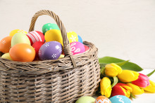 Colorful Easter Eggs In Basket And Tulips On White Wooden Table, Closeup
