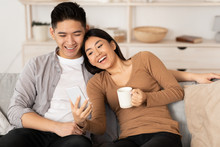 Asian Couple Resting On Couch,...