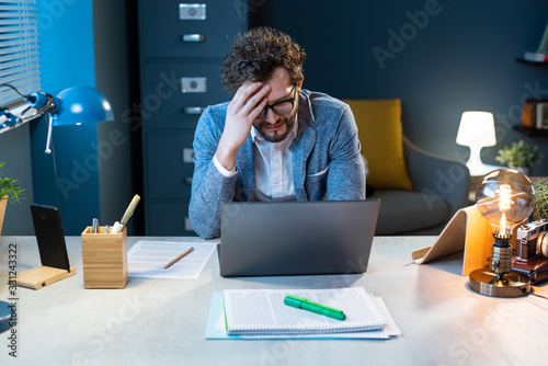 Foto Stressed businessman working in the office