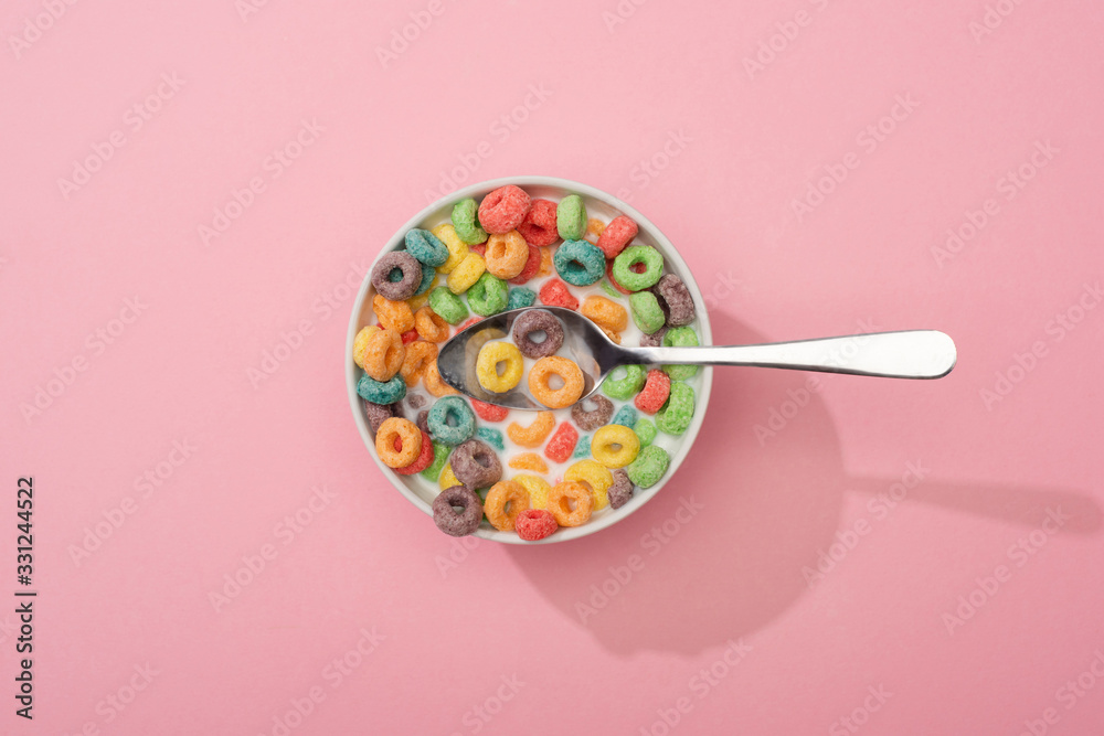 Fototapeta top view of bright colorful breakfast cereal in bowl with spoon on pink background