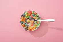 Top View Of Bright Colorful Breakfast Cereal In Bowl With Spoon On Pink Background