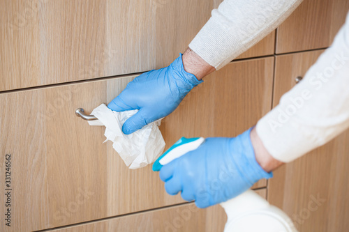 man hands in gloves disinfecting chest of drawers handle, killing virus on surfa Canvas Print