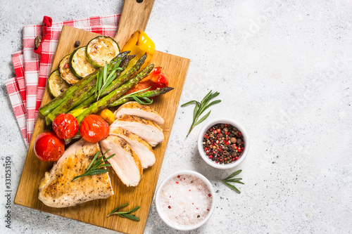 Fotografie, Obraz Chicken breast grilled with vegetables on a wooden serving board.