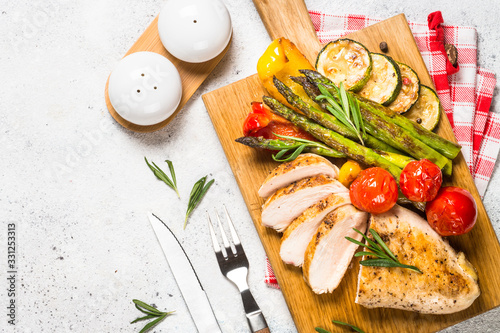 Fototapeta Chicken breast grilled with vegetables on a wooden serving board.