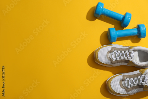 Foto Dumbbells, sneakers and space for text on yellow background, flat lay
