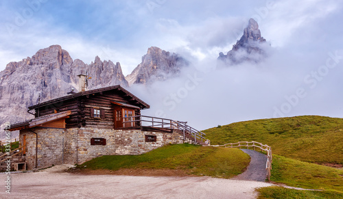Wall mural - Fantastic misty landscape of Dolomites mountains. Amazing Alpine scenery Baita Segantini mountain refuge with Cimon della Pala peak. Beautiful nature Scenery. Dolomites Alps. Italy. Europe
