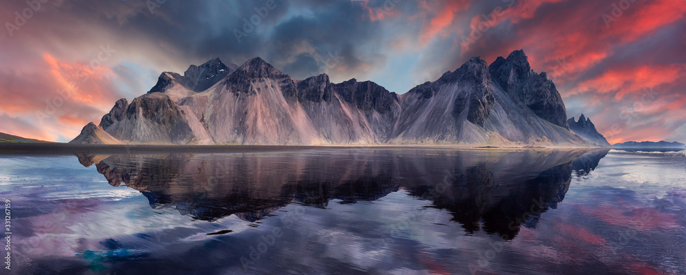 Fototapeta Vestrahorn mountaine on Stokksnes cape in Iceland during sunset with reflections. Amazing Iceland nature seascape. popular tourist attraction. Best famouse travel locations. Scenic Image of Iceland