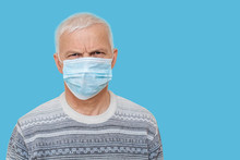 Elderly Man In Protective Medical Mask Isolate In Blue. Coronavirus Elderly Advice. Safety Old Men.