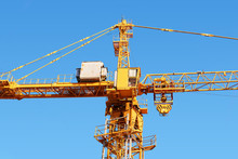 Fragment Of A Construction Tower Crane With A Cabin Against A Blue Sky