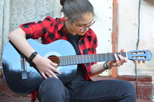 A Young Girl With Glasses And Her Hair In A Bun Plays A Classic Black Guitar Sitting On The Porch Of An Old House. The Girl Is Wearing A Red-and-black Checked Shirt And Black Jeans. Selective Focus.
