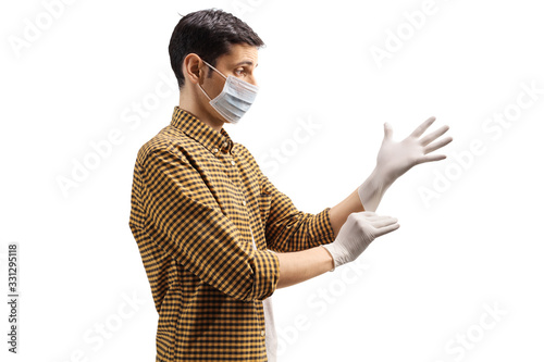 Fotografie, Obraz Profile shot of a man wearing a surgical mask and putting medical gloves