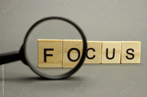 Obraz The word focus is made of wooden letters with a magnifying glass. Selective focus - fototapety do salonu