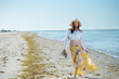 canvas print picture - Middle age woman over 50 in yellow skirt with long hair walking alone on a Florida beach
