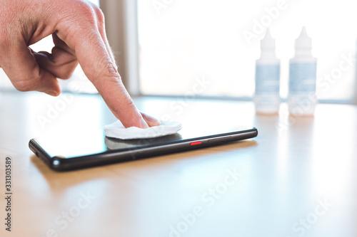 Fotografie, Obraz Coronavirus, pulizia smartphone con alcool a casa per disinfettare la superficie