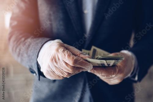 Man counting Polish zloty money banknotes in protective latex gloves Fototapeta
