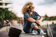 Beautiful adult caucasian young woman with blonde curly hair enjoy the outdoor leisure activity relaxing and sitting on a wall with bike in background - people portrait with sky in background