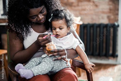 Fotografiet Loving mother spoon feeding cute newborn daughter