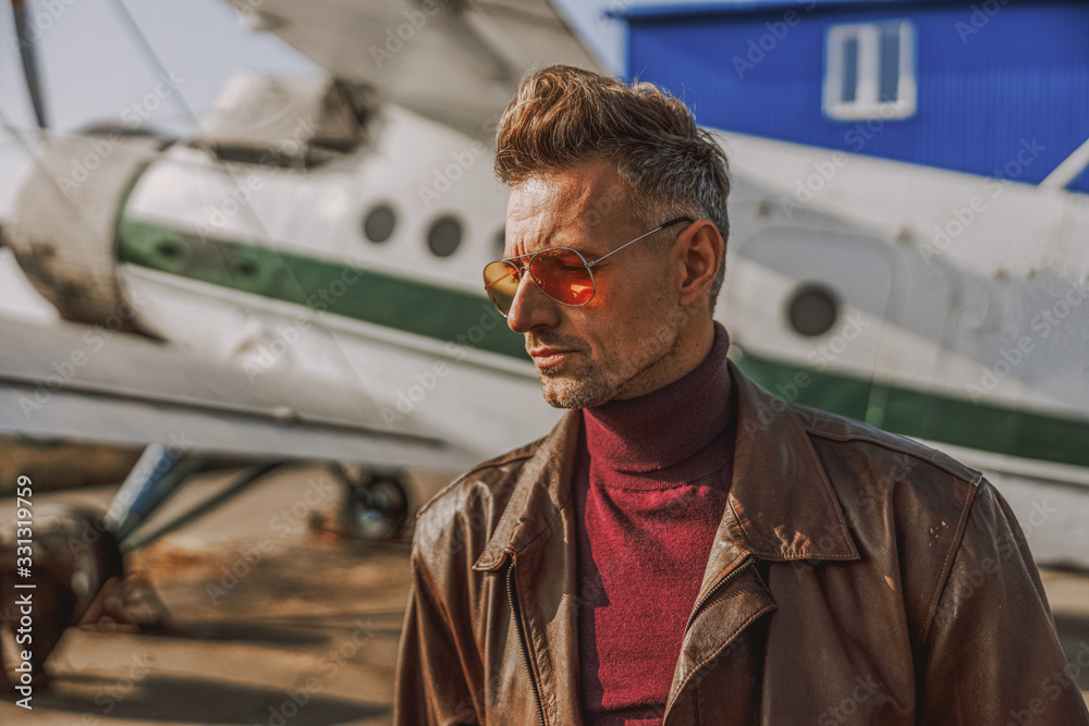 Fototapeta Fashionable adult man is staying near airplane