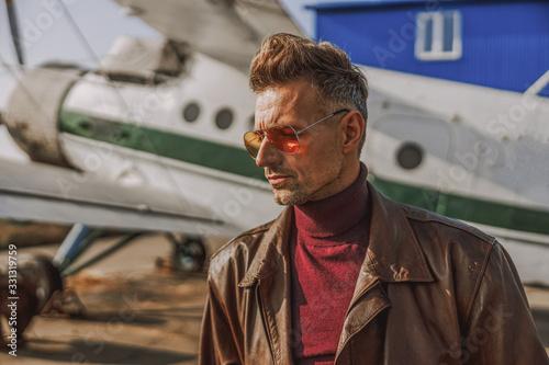 Fashionable adult man is staying near airplane