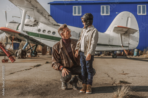Obraz na plátně Smiling man and his son looking each other near plane