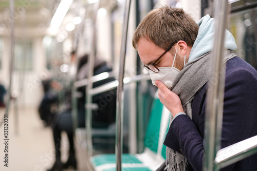 Fotografía Ill man in glasses feeling sick, coughing, wearing respirator N95 mask against t