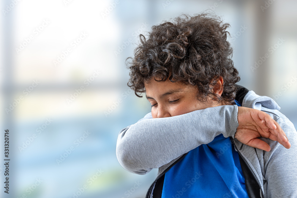 Fototapeta yong boy teenager sneezing into his elbow.,to avoid infecting others
