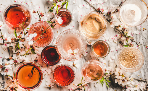 Fototapeta Various shades of rose wine. Flat-lay of rose wine in different colors in glasses and spring blossom flowers over marble background, top view. Wine shop, bar, tasting, seasonal wine list concept obraz