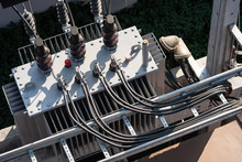 Top View Of High Voltage Power Transformer With Electrical Insulation And Electrical Equipment In Power Substation.