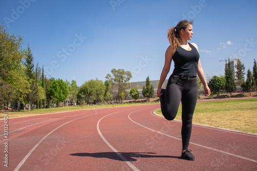 Photo Mujer Fitness con ropa negra en pista de tartán realizando ejercicios de calenta