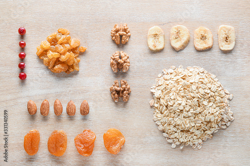 fototapeta na drzwi i meble Dry oat grains with fruits and nuts on wooden background