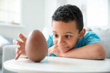 Cute African-American Boy With Sweet Chocolate Egg At Home