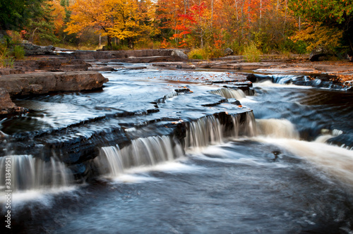 The Sturgeon River spills over a ledge waterfall as it flows through a landscape of peak autumn color in Michigan's Upper Peninsula.