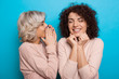 Close up portrait of a caucasian blonde girl whispering something to her curly haired friend while posing on a blue background
