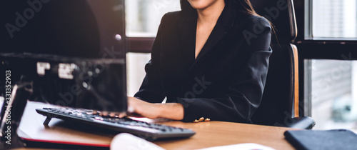 Fotografía Confident asian businesswoman relaxing looking at technology of desktop computer while sitting on office desk