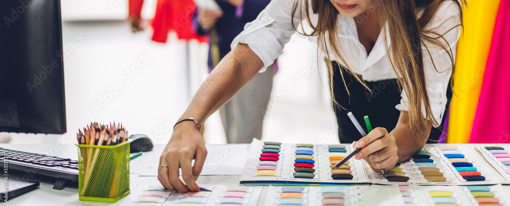 Fototapeta Portrait of young beautiful pretty woman fashion designer stylish stand and working with color textile samples.Attractive  senior woman working with mannequins and colorful fabrics at fashion studio