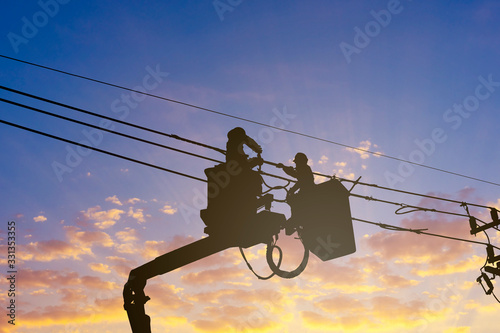 Obraz silhouette maintenance of electricians work with high voltage electricity on the hydraulic bucket - fototapety do salonu