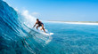 Young man surfs ocean wave in Maldives