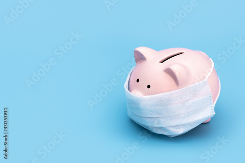 Fototapeta Pink piggy Bank stands on a blue medical background in a medical mask, on the right there is an empty space for the text. Chinese Coronavirus, 2019-nCoV obraz