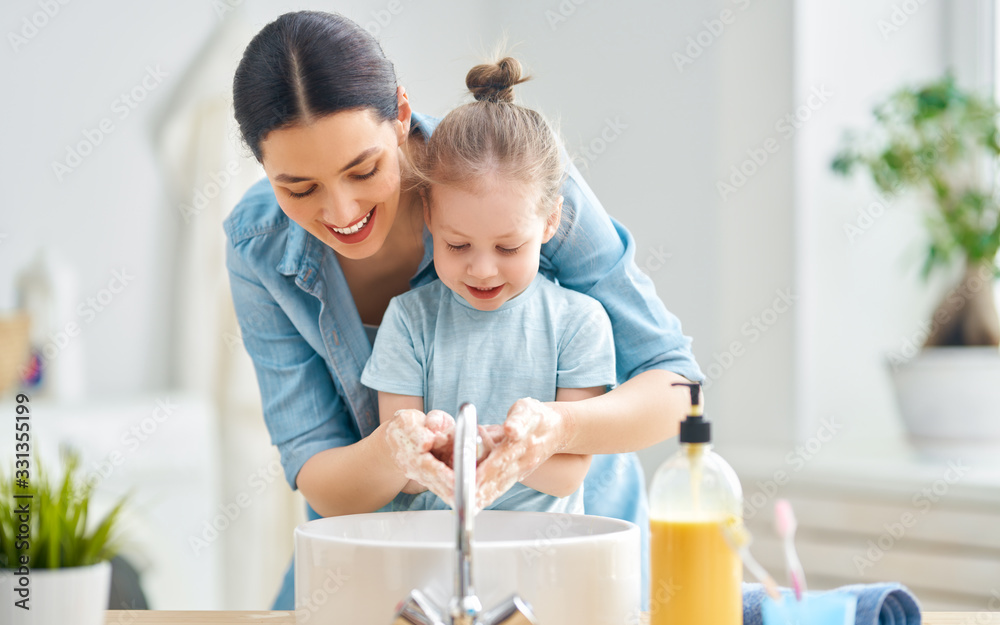 Fototapeta girl and her mother are washing hands