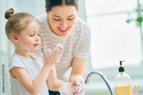 girl and her mother are washing hands - 331355111