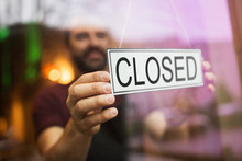 Small Business, People And Crisis Concept - Owner Puts Closed Sign At Bar Or Restaurant Glass Door Or Window