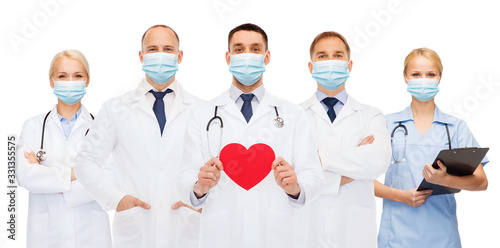 Obraz medicine, cardiology and healthcare concept - group of doctors wearing protective medical masks with red heart and stethoscopes over white background - fototapety do salonu